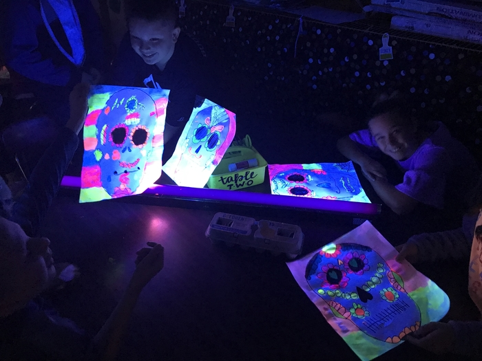 4th graders in Miss Brady's art class doing glow-in-the-dark artwork!
